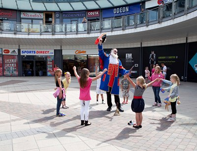 The World's tallest Town Cryer Martin Wood officially announces the start of Wrexham's Year of Culture Street Entertainment Festival Competition at  Eagles Meadow in Wrexham. Pictured: Martin Wood attracts the attention of a group of youngsters on their way to a party