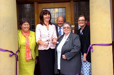 Lesley Griffiths AM cuts the ribbon at the opening of Hillbury House watched byLiz Rees, Mario Kreft, Anita Curley and Barbara Hale